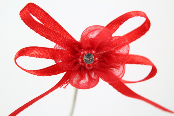 Our vibrant red chiffon flower bow with adhesive pad